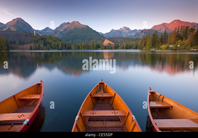 Rowing boats and mountains beneath a twilight sky, Strbske Pleso Lake in the High Tatras, Slovakia, Europe. - Stock Image