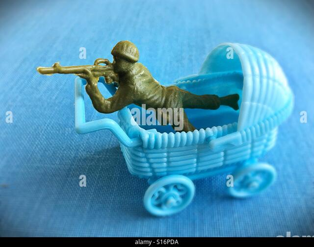 A toy soldier and a toy baby buggy. - Stock Image