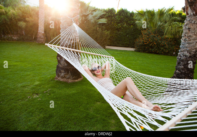 Teenage girl lounging on hammock - Stock-Bilder