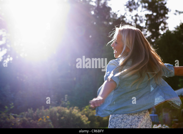 Austria, Teenage girl dancing in sunlight - Stock Image