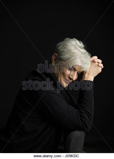 Confident, smiling senior woman with short white hair looking down against black background - Stock Image