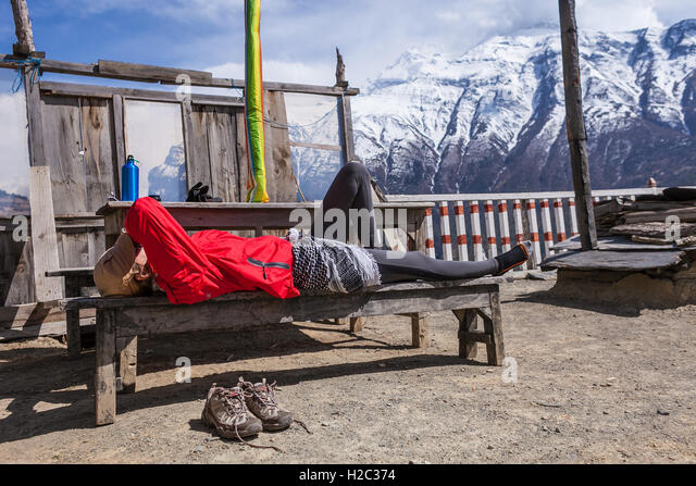 Beautiful Woman Traveler Backpacker Take Rest Mountain Terrace Village.Young Girl Sleeping Bench.North Snow Peaks - Stock Image