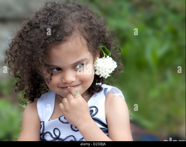 a young multi ethnic child is shy and timid expression - Stock Image