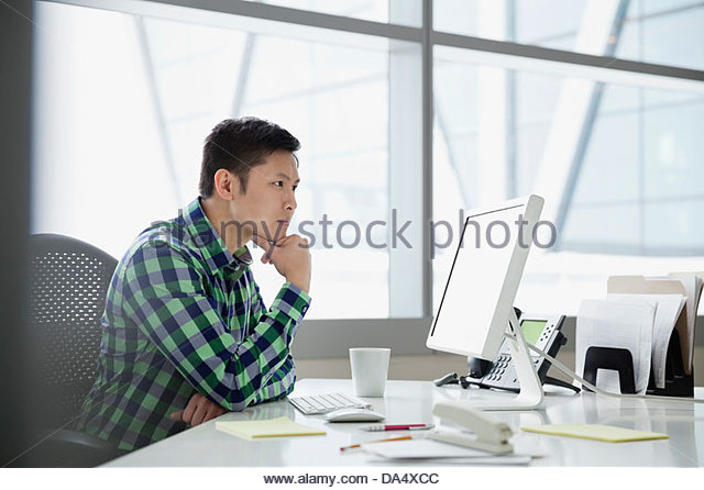 Businessman looking at computer monitor in office - Stock Image
