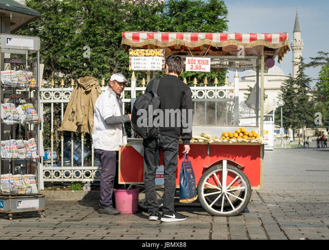 Istanbul, Turkey - April 16, 2017: Tourist buying fast food meal from a traditional Turkish chestnut and corn cart - Stock Image