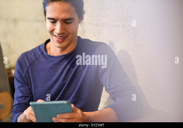 Young man using digital tablet, indoors - Stock Image