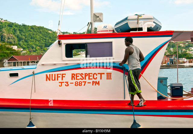 grenada st georges carenage careenage capital city working harbor harbour man washing boat hose - Stock Image