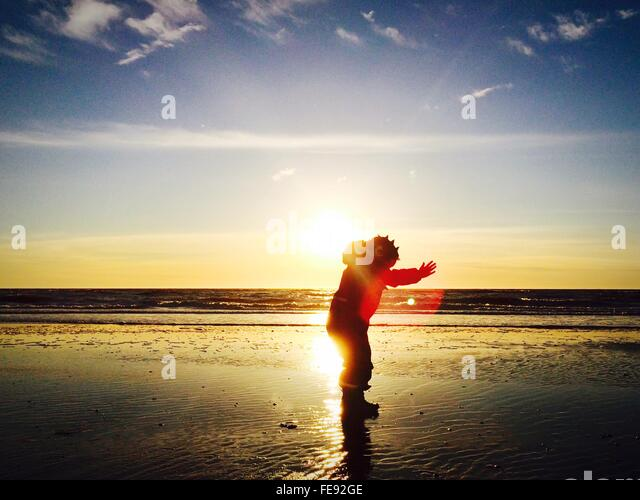 Man Wearing Costume Standing At Beach Against Sky During Sunset - Stock Image