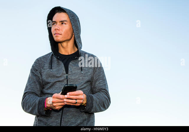 Mixed Race man wearing hoody texting on cell phone - Stock-Bilder