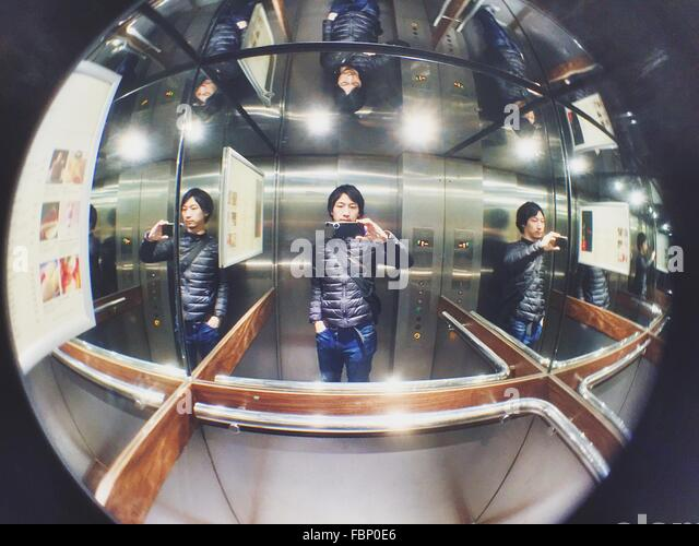 Man Taking Selfie In Elevator - Stock Image
