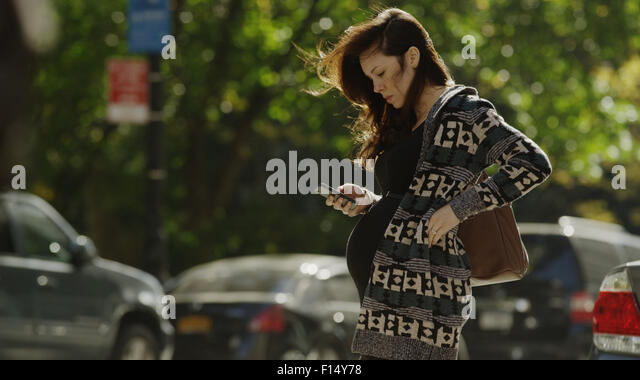 Side view of focusing pregnant woman using cell phone and crossing city street - Stock Image
