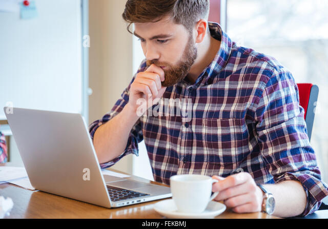 Serious focused bearded young man in checkered shirt sitting at the table and using laptop - Stock Image