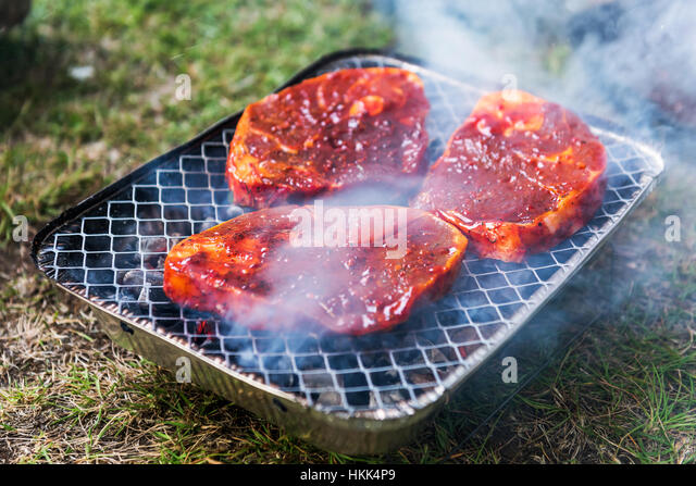 striped mutton steak on non-permanent foil grill closeup - Stock Image