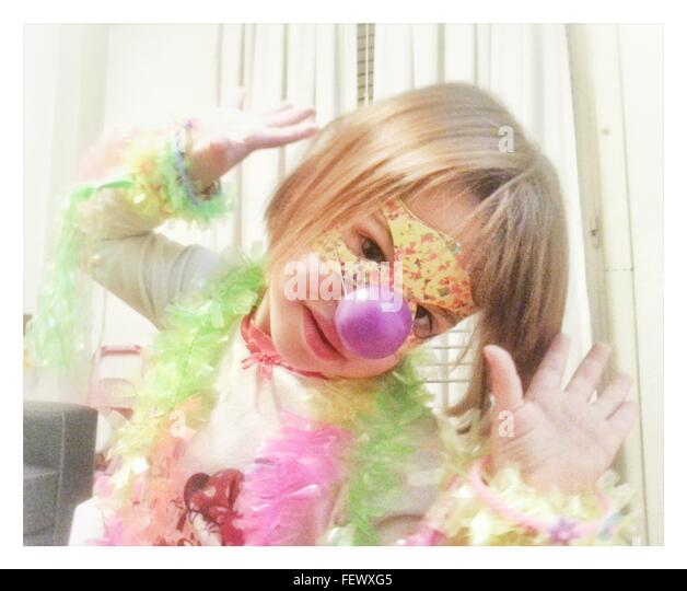 Portrait Of Cute Girl Wearing Mask At Home - Stock Image