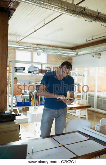 Designer with digital tablet standing over plans on office desk - Stock Image