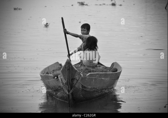 Children rowing boat, Tonle Sap Lake, Cambodia - Stock Image