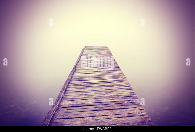 Vintage filtered picture of old wooden pier in dense fog with strong vignette effect. - Stock-Bilder