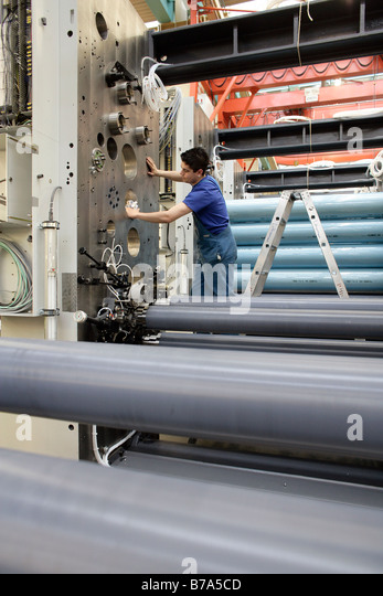 Laborer cleaning the impression cylinders of a reel-fed offset printing machine, manufacture, Production MAN Roland - Stock Image
