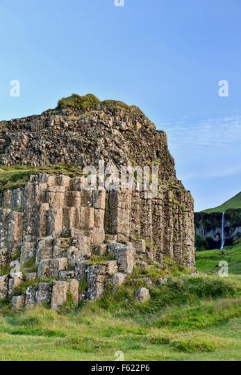 Columnar basalt outcrop (and waterfall in background), Dverghamrar (Dwarf Cliffs), near Foss, Iceland - Stock-Bilder