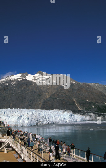Alaska Cruise Glacier Bay with huge glacier in background comparative size with ship passengers on deck - Stock Image