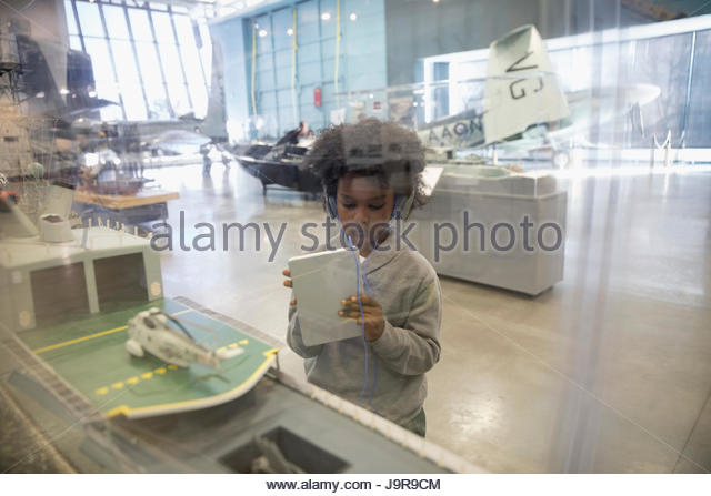 Curious boy with headphones and digital tablet looking at model Naval ship exhibit on field trip in war museum - Stock-Bilder