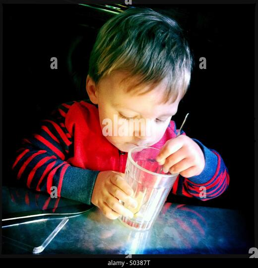 Young boy looking closely at what he has left to drink - Stock Image