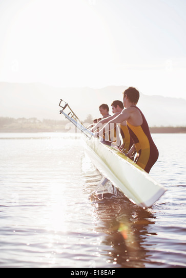 Rowing team placing boat in lake - Stock Image