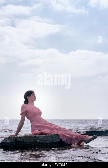 a woman in a pink dress is sitting on stones at the sea - Stock Image