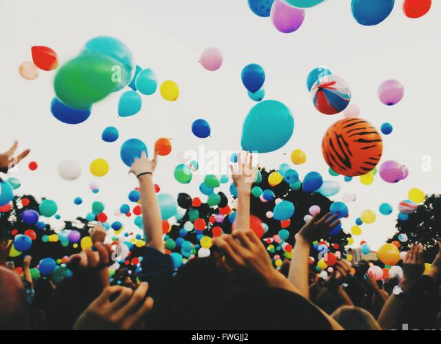 Crowd throwing colorful balloons against sky during festival - Stock Image