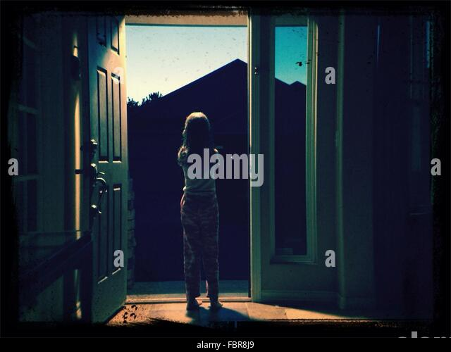 Full Length Rear View Of Girl Standing At Entrance At Home - Stock Image