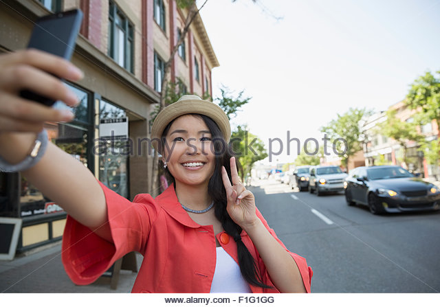 Smiling woman with hat gesturing peace sign taking selfie - Stock-Bilder
