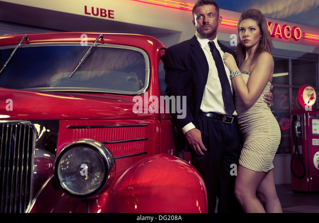 Well dressed man and woman next to antique red car in front of service station - Stock Image