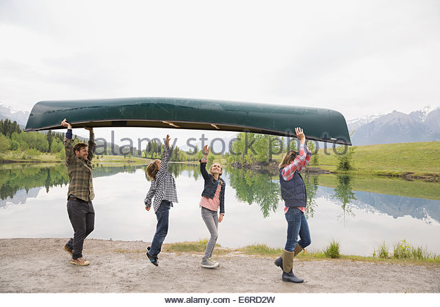 Family carrying canoe by still lake - Stock Image