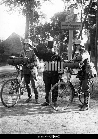 A chimney sweeper shows the way to two soldiers - Stock Image