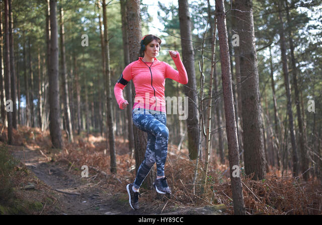 A woman running downhill in the woods - Stock Image