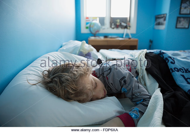 Boy sleeping in bed - Stock Image