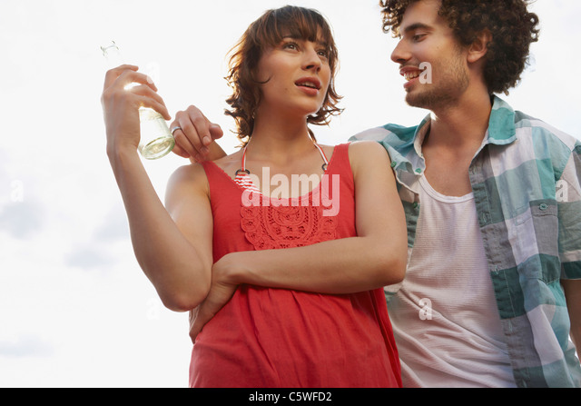 Germany, Berlin, Young couple, woman holding bottle, low angle view, portrait - Stock Image