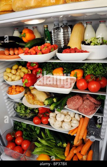 VIEW INSIDE REFRIGERATOR WITH SHELVES FILLED WITH FRESH FOOD - Stock Image