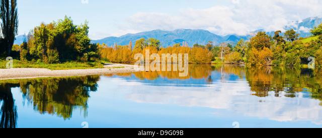 Reflection of autumn trees on the Takaka River, Golden Bay, Tasman Region, South Island, New Zealand - Stock Image