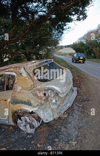 a car crashed and burnt out in a rural lane in cornwall,uk - Stock Image