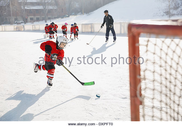 Hockey player practicing on ice rink - Stock Image