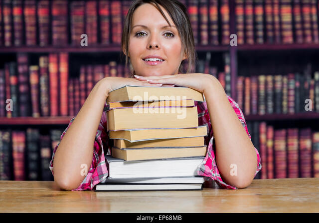 Portrait of college student sitting with stack of books in library - Stock Image