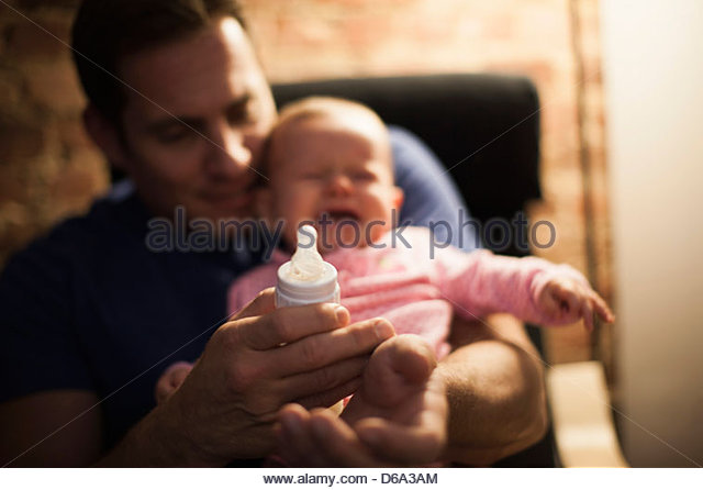 Father feeding crying baby daughter - Stock-Bilder