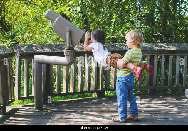 Young boy (4-5) helping girl (2-3) looking through telescope - Stock Image