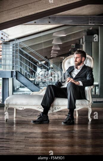 Mid adult man wearing suit sitting on chaise lounge looking away - Stock-Bilder