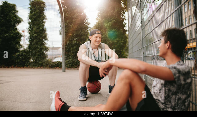 Young friends sitting on basketball court. Streetball players taking rest after playing a game. Two young men relaxing - Stock Image