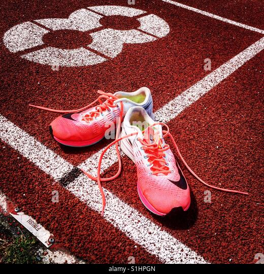Trainers on running track finish line - Stock Image