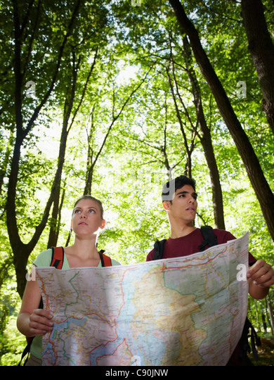 young man and woman got lost during hiking excursion and look for destination on map. Vertical shape, waist up - Stock Image