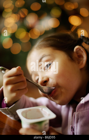 Five year old girl eats yoghurt from pot - Stock Image