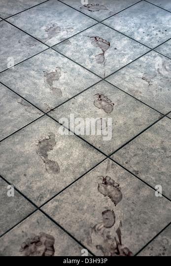 bloody footprints on a bathroom floor - Stock Image